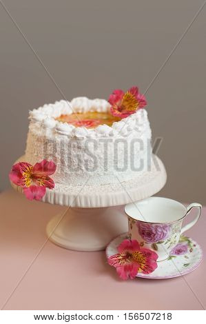 cake with whipped cream on a stand, tea accessories in the background