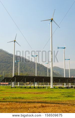 solar panels with wind turbines against mountanis landscape against blue sky
