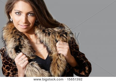 Portrait of sexy female in fashionable coat posing during photoshoot