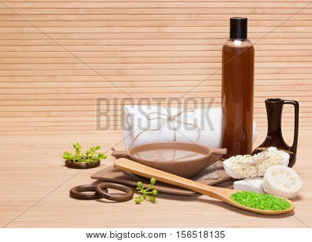 Natural spa. Pampering bath and body care products and accessories: sea salt, pumice, loofah, body scrubber, bamboo plate with water, crock, shower gel, terry cloth towel on wooden surface. Copy space