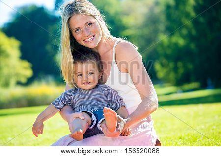 Barefoot Toddler Sitting In Lap Of Smiling Woman