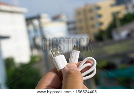 Micro USB white color in human hand.