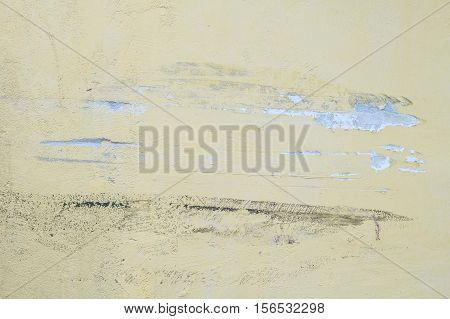 Closeup pale color and peeling of painted yellow cement wall textured background damaged by car