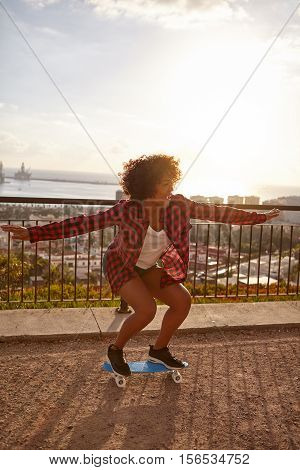 Skateboarding girl with her arms out and knees bent on a bridge overlooking a city with a bay further behind wearing casual clothing
