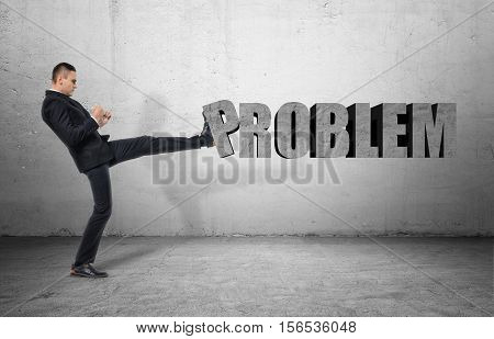 A businessman full-height in profile, kicking a big word 'PROBLEM', on the grey background. Business and management. Solving problems. Poses and gestures.