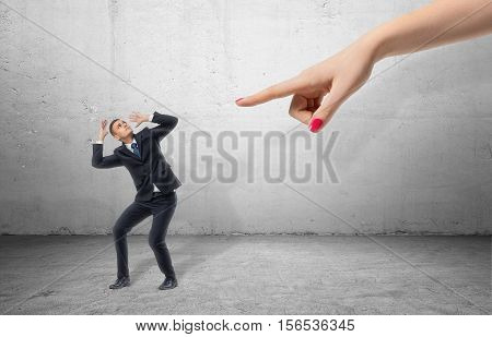 A scared businessman full-height in a desperate pose and a giant hand pointing at him, on the grey background. Business and management. Employment issues. Getting fired. Being told off.