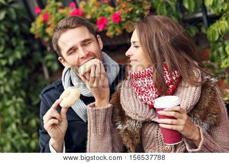 Picture showing young couple on date in the city with coffee and donuts