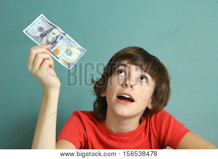 preteen boy with one hundred dollar bill think what to buy close up photo