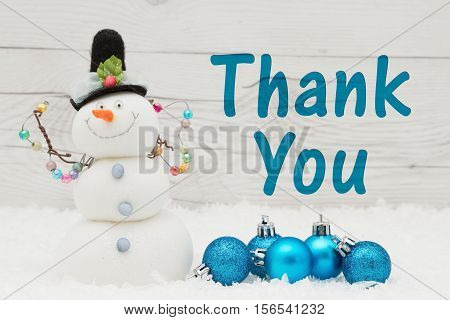 Thank you message Some snow Christmas ornaments and a snowman on weathered wood with text Thank You