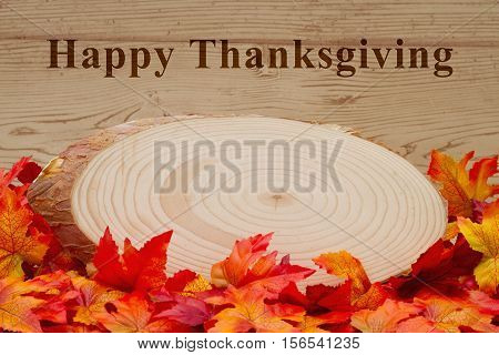 Happy Thanksgiving greeting Some fall leaves and wood plaque on weathered wood with text Happy Thanksgiving