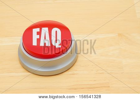A FAQ red push button A red and silver push button on a wooden desk with text FAQ