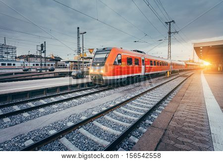 Railway Station With Beautiful Modern Red Commuter Train At Sunset