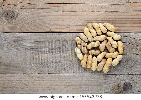 Roasted peanuts in shell on wooden table top view