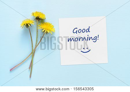 Dandelion flowers and paper with Good morning text on blue table