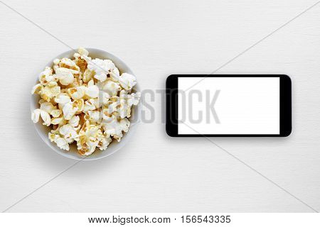 Popcorn and smartphone on white table top view