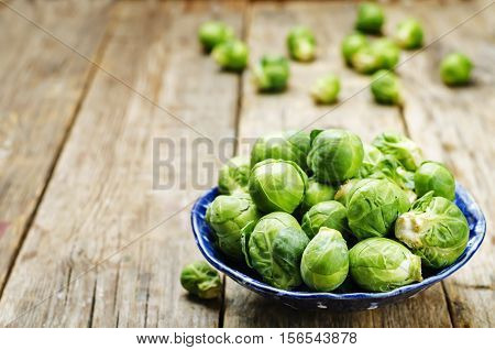 Brussels sprouts in a wooden bowl on wood background