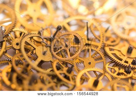 A pile of gears background. Many mechanisms. Old vintage gears. Part of clockwork. The natural color and texture. Focus on front blurred background. Golden cogs