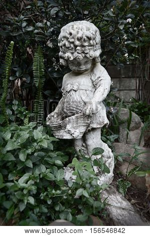Concrete statue of shy girl in garden