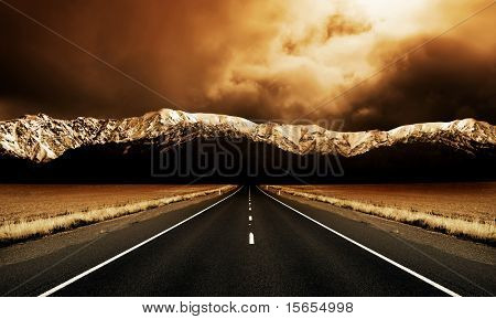 Long straight road heading to stormy mountains