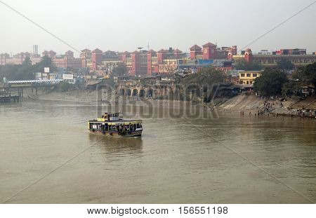 KOLKATA, INDIA - FEBRUARY 10: Ferry boat crosses the Hooghly River nearby the Howrah Bridge in Kolkata on February 10,2016. To use the ferry is easy, fast and cheap way how to cross the Hooghly River.