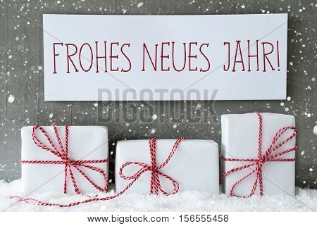 Label With German Text Frohes Neues Jahr Means Happy New Year. Three Christmas Gifts Or Presents On Snow. Cement Wall As Background With Snowflakes. Modern And Urban Style.