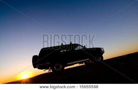 A 4wd climbs a hill at sunrise