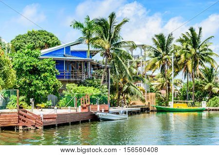 Placencia, Belize - August 28 2016: Tropical waterside house with moored boats on lagoon side of Placencia in Belize, Central America