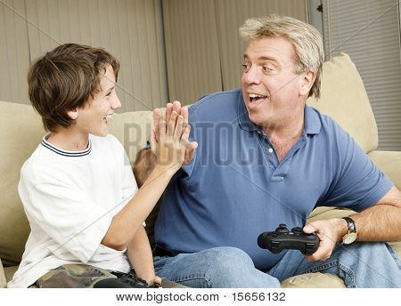 Uncle giving his nephew a high five as they play video games.  Could also be father and son.