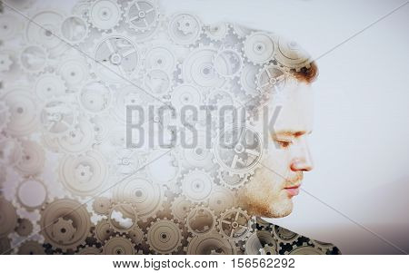 Side portrait of young businessman with cogwheels on light background. Brainstorming concept. Double exposure
