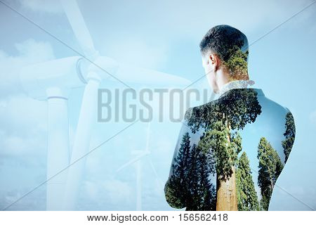 Thoughtful businessperson on sky background with wind mills. Double exposure. Eco friendly business concept
