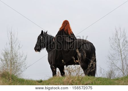 Brave woman with red hair in black cloak on a purebred friesian horse girl from the back