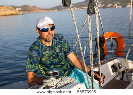 Male skipper sitting on his sailing yacht near the rigging.