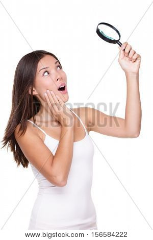 Funny shocked woman searching finding clues with magnifying glass. Surprised Asian girl looking astonished discovering shocking news or secrets, studio portrait isolated on white background.