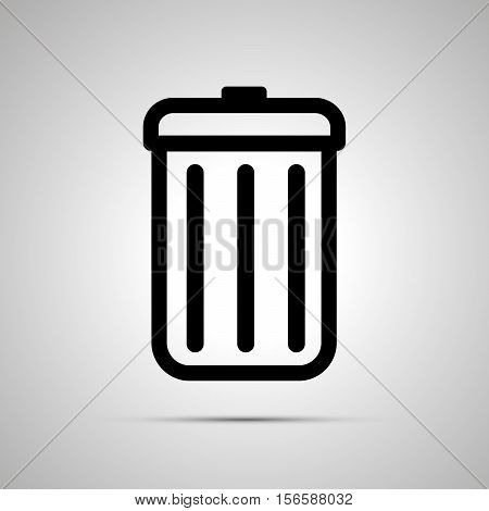 Simple black icon of trash can with shadow on light background