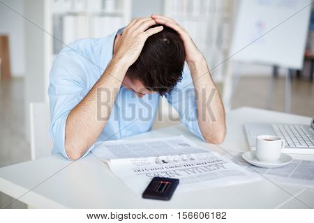 Frustrated businessman reading a newspaper, his smart phone with low battery icon lying on table near him