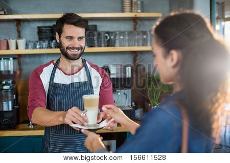 Waiter serving a cup of cold coffee to customer at counter in cafe