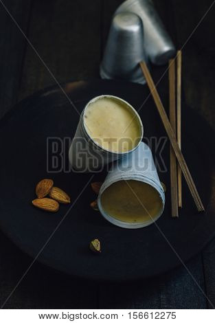 Kulfi - An authentic and popular Indian street dessert made with sweet condensed milk with fresh nuts. Frozen Kulfis placed on an earthen plate with whole nuts on dark background.