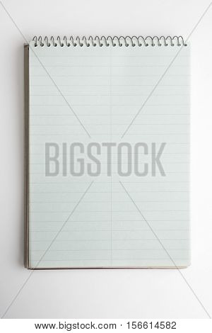 A vertical to-do list type note book, isolated on natural white background. Intentionally shot with shadow and highlight on bottom left corner.