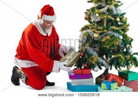 Santa claus arranging presents near christmas tree against white background