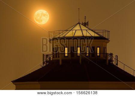 Lit full moon over tower Prague Czech Republic