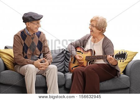 Mature man sitting on a sofa and looking at a mature woman playing on a guitar isolated on white background