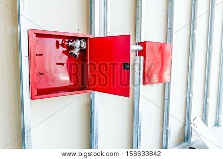 Red fire hydrant cabinet with extinguish valve is placed in an unfinished dry wall.