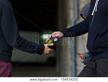 drug trafficking, crime, addiction and sale concept - close up of addict buying dose from dealer