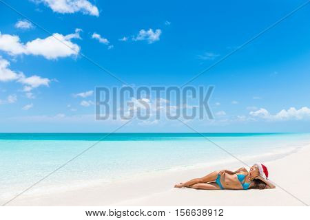 Relaxing christmas vacation woman lying down on perfect white sand sunbathing. Santa hat woman relaxing on paradise beach island getaway.