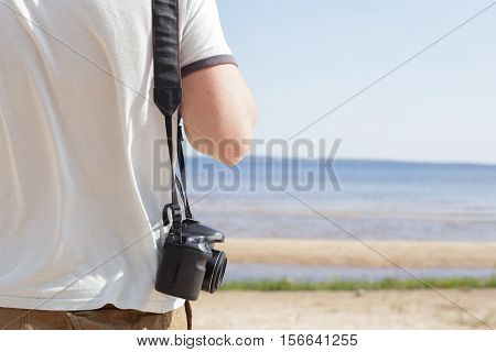 Man (male) dressed in shirt and breeches standing on sandy shore of sea and holding camera