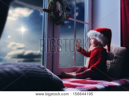 Merry Christmas and happy holidays! Cute little baby girl sitting by the window and looking at the christmas star. Room decorated on Christmas. Kid enjoys the night sky.