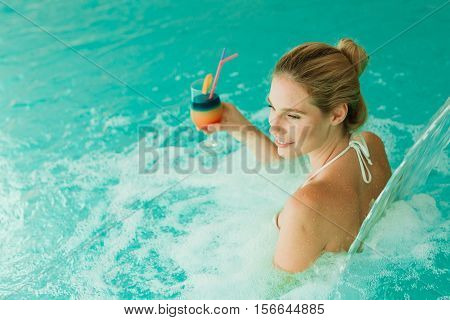 Woman enjoying hydrotherapy and cocktail in spa pool
