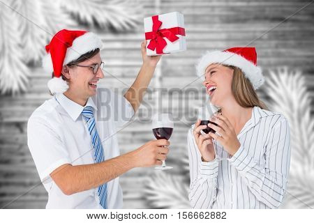 Happy couple in santa hat holding gift and glass of wine during christmas time