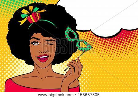 Pop art face. Young sexy afro american woman with gift on her head and carnival mask in her hand smiles and winks with speech bubble. Vector illustration in retro comic style. Party invitation.