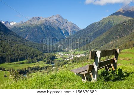 Bench overlooking Lower Engadine Alpine valley in Switzerland on a sunny summer day
